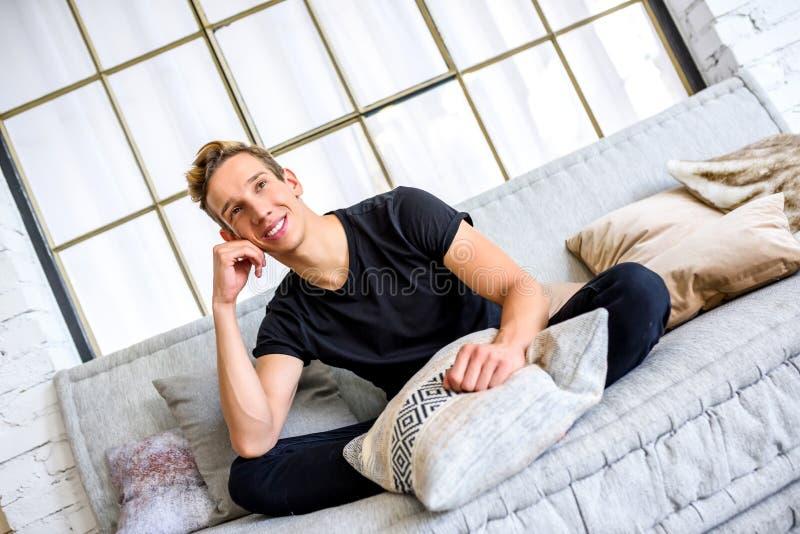 Ein junger gutaussehender Mann, der auf dem Sofa in einem Dachbodenart apartm sich entspannt lizenzfreies stockbild
