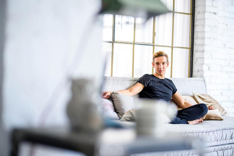Ein junger gutaussehender Mann, der auf dem Sofa in einem Dachbodenart apartm sich entspannt stockfoto