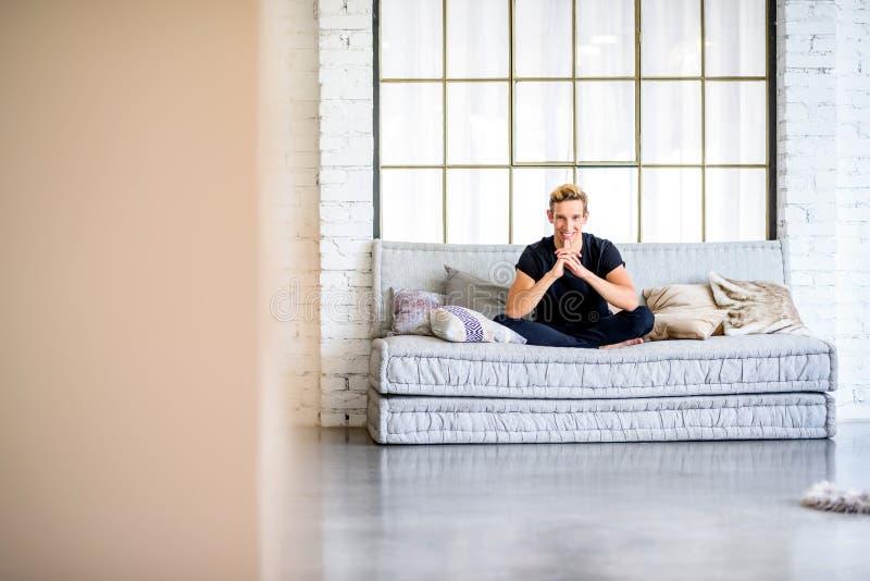Ein junger gutaussehender Mann, der auf dem Sofa in einem Dachbodenart apartm sich entspannt lizenzfreie stockfotografie