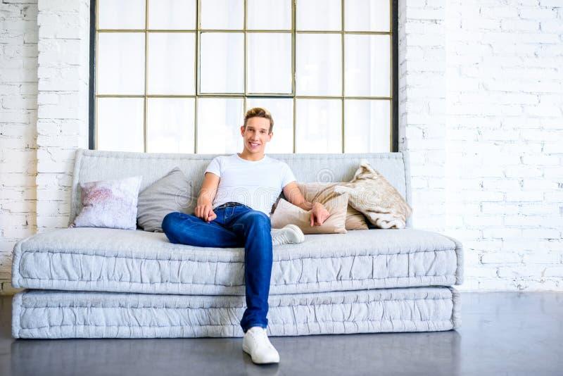 Ein junger gutaussehender Mann, der auf dem Sofa in einem Dachbodenart apartm sich entspannt lizenzfreies stockfoto