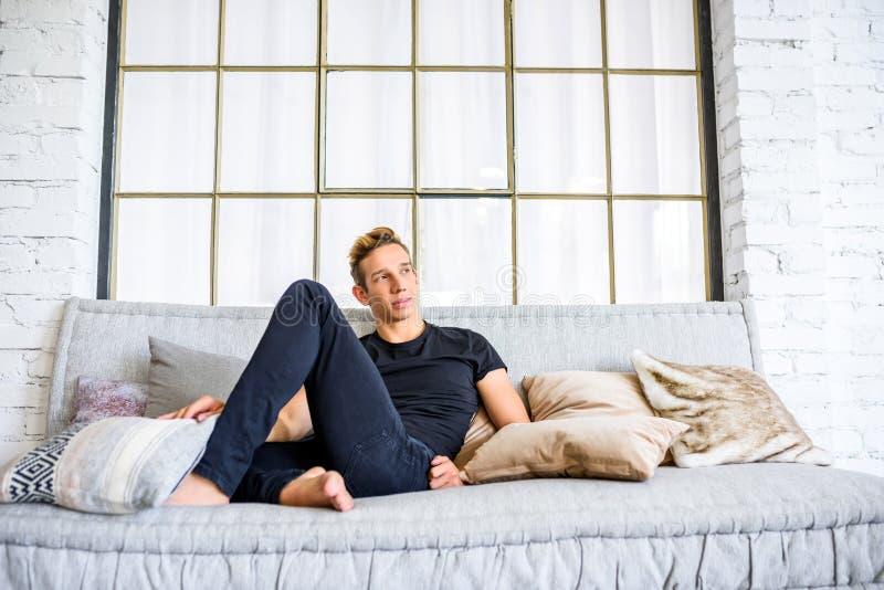 Ein junger gutaussehender Mann, der auf dem Sofa in einem Dachbodenart apartm sich entspannt lizenzfreie stockbilder