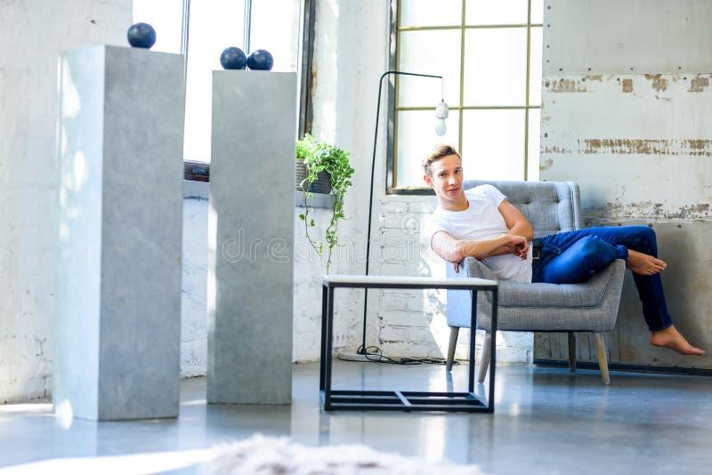 Ein junger gutaussehender Mann, der in einem Lehnsessel in einem Dachbodenart-APAR sich entspannt stockfotografie