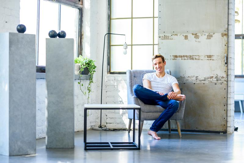 Ein junger gutaussehender Mann, der in einem Lehnsessel in einem Dachbodenart-APAR sich entspannt lizenzfreies stockbild