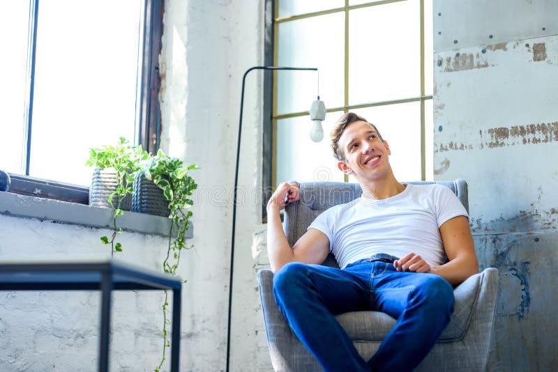 Ein junger gutaussehender Mann, der in einem Lehnsessel in einem Dachbodenart-APAR sich entspannt stockfoto