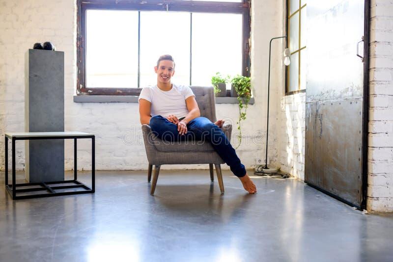 Ein junger gutaussehender Mann, der in einem Lehnsessel in einem Dachbodenart-APAR sich entspannt lizenzfreies stockfoto