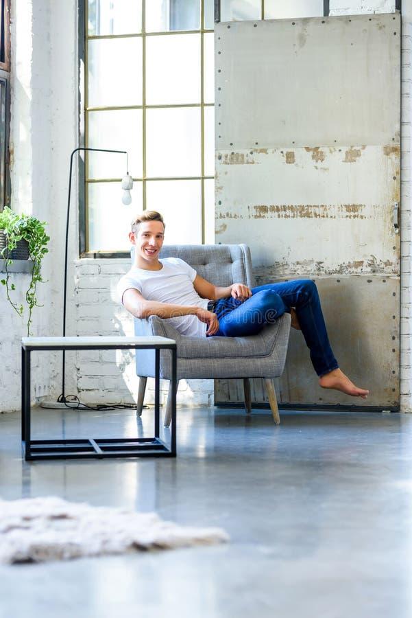 Ein junger gutaussehender Mann, der in einem Lehnsessel in einem Dachbodenart-APAR sich entspannt stockbild