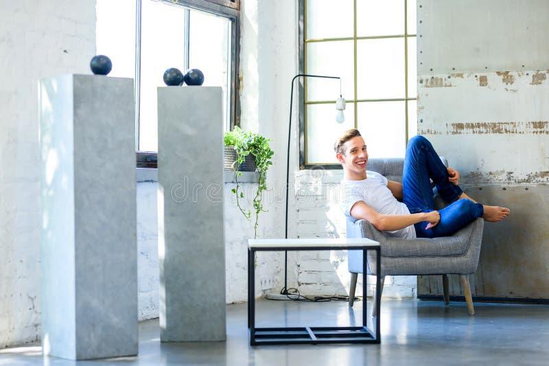 Ein junger gutaussehender Mann, der in einem Lehnsessel in einem Dachbodenart-APAR sich entspannt stockfotos