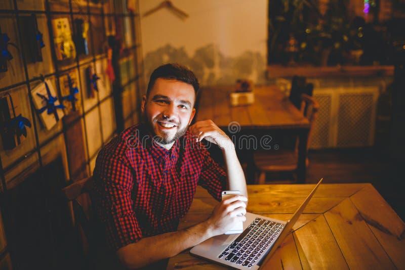 Ein junger hübscher kaukasischer Mann mit Bart und toothy Lächeln im roten karierten Hemd arbeitet hinter dem Laptop, der am Holz stockfotos
