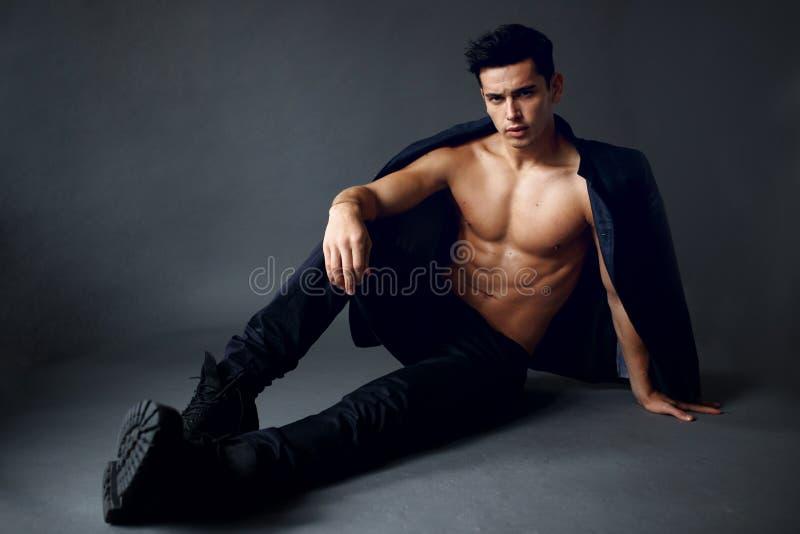 Ein junger, h?bscher, sexy Mann mit Jacke auf seinen Schultern, auf dem nackten Torso, Sitzen auf grauem Hintergrund aufwerfend,  lizenzfreie stockfotos