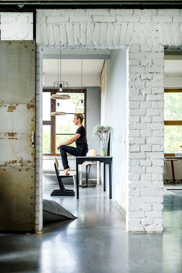 Ein junger hübscher Tänzer, der in einer Dachbodenartwohnung sich entspannt stockbilder