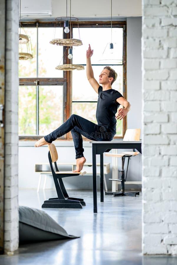 Ein junger hübscher Tänzer, der in einer Dachbodenartwohnung sich entspannt stockfotografie