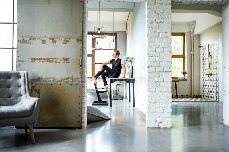Ein junger hübscher Tänzer, der in einer Dachbodenartwohnung sich entspannt lizenzfreie stockfotografie