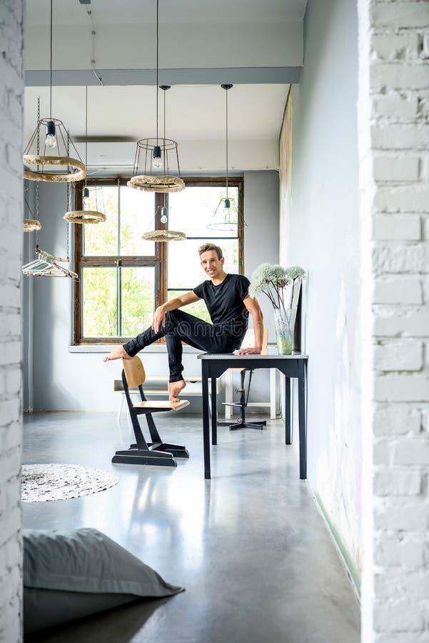 Ein junger hübscher Tänzer, der in einer Dachbodenartwohnung sich entspannt lizenzfreies stockfoto