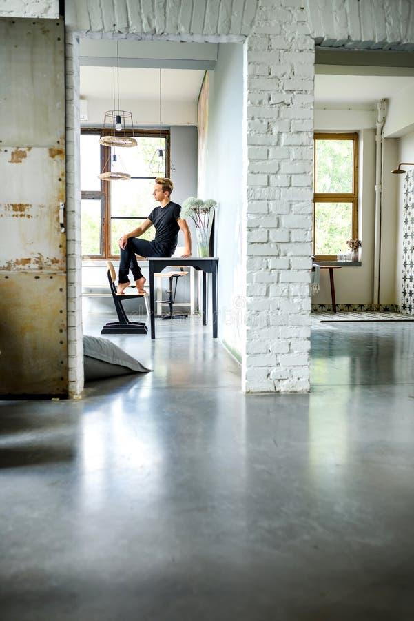 Ein junger hübscher Tänzer, der in einer Dachbodenartwohnung sich entspannt lizenzfreie stockbilder
