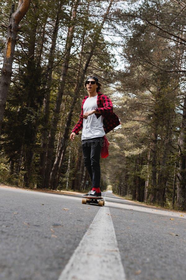 Ein junger Hippie in einer Kappe und in einem karierten Hemd reitet sein longboard auf eine Landstraße im Wald lizenzfreie stockfotos