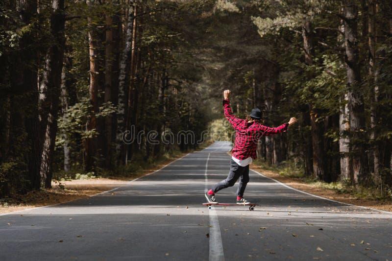 Ein junger Hippie in einer Kappe und in einem karierten Hemd reitet sein longboard auf eine Landstraße im Wald stockbild