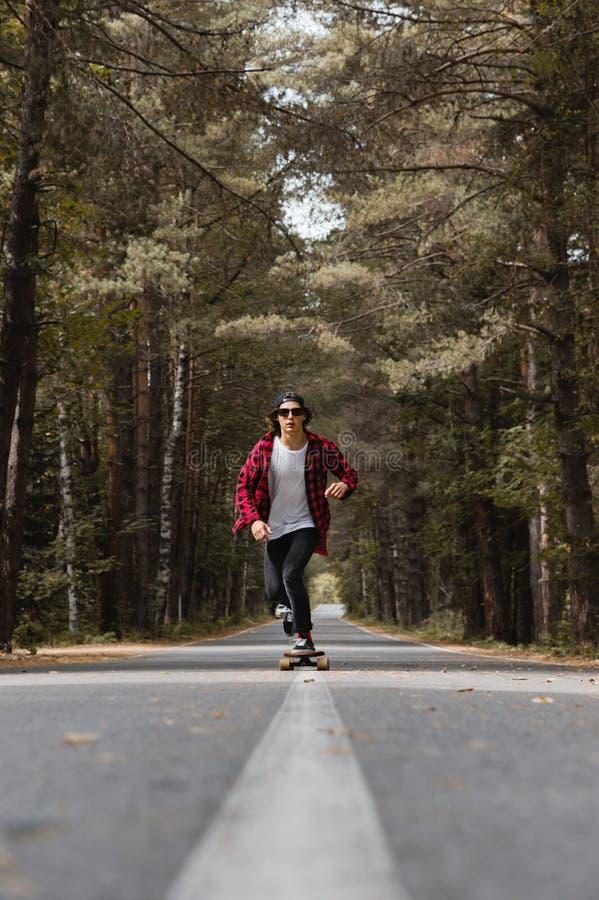 Ein junger Hippie in einer Kappe und in einem karierten Hemd reitet sein longboard auf eine Landstraße im Wald stockfoto
