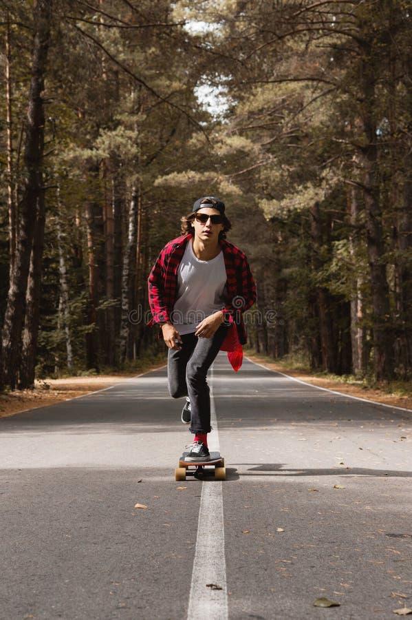 Ein junger Hippie in einer Kappe und in einem karierten Hemd reitet sein longboard auf eine Landstraße im Wald stockfotos