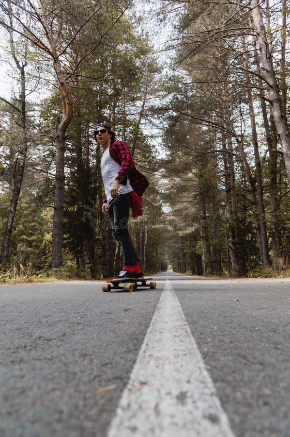 Ein junger Hippie in einer Kappe und in einem karierten Hemd reitet sein longboard auf eine Landstraße im Wald lizenzfreies stockfoto