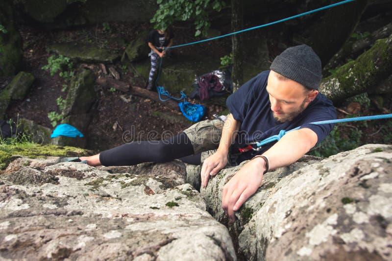 Ein junger Hippie nimmt an Klettern mit Versicherung auf Felsen mit grünem Moos teil stockbild