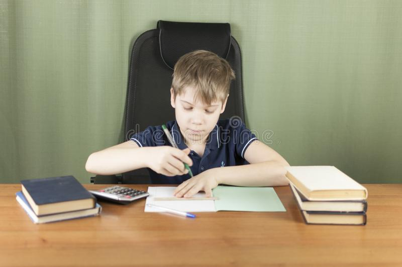 Ein junger Junge arbeitet an seiner Heimarbeit am Tisch Zurück zu Schule-Konzept Idee und Kreativitätskonzept Copyspace lizenzfreie stockfotos