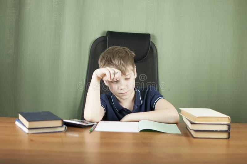Ein junger Junge arbeitet an seiner Heimarbeit am Tisch Zurück zu Schule-Konzept Idee und Kreativitätskonzept Copyspace lizenzfreie stockfotografie