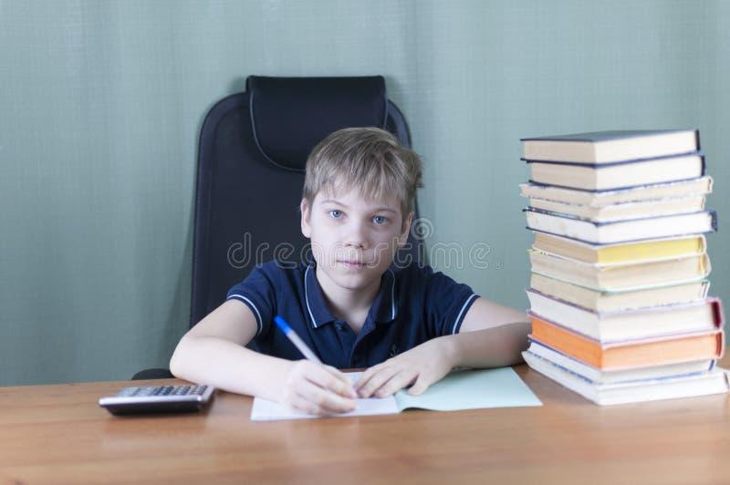 Ein junger Junge arbeitet an seiner Heimarbeit am Tisch Zurück zu Schule-Konzept Idee und Kreativitätskonzept Copyspace lizenzfreie stockbilder