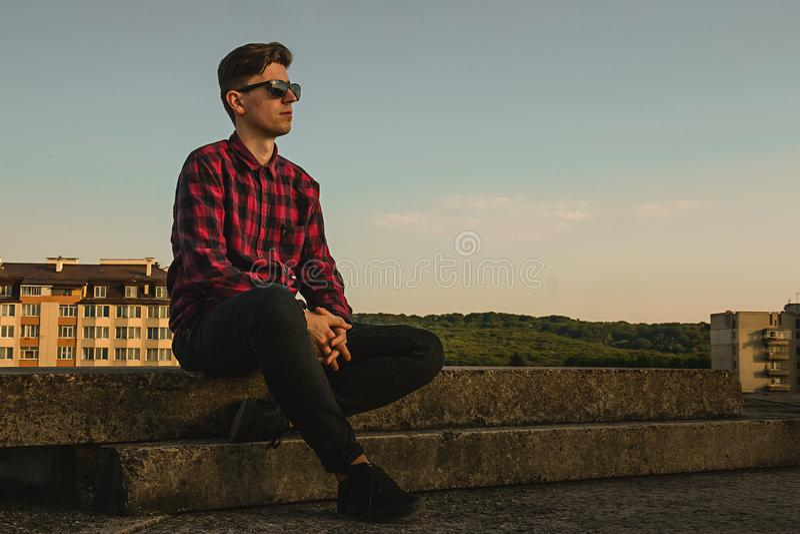Ein junger kühler Kerl in den Hippies Hemd und Sonnenbrille auf dem Dach mit blauem Himmel und Wolken stockfotos