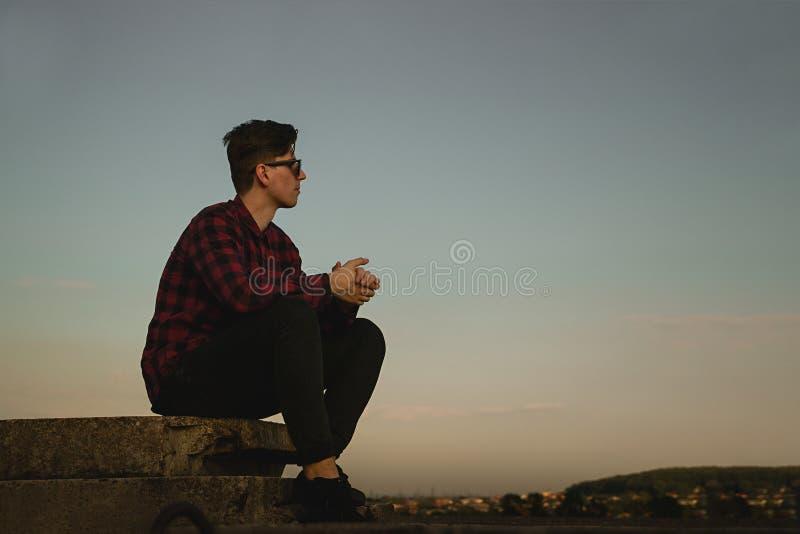 Ein junger kühler Kerl in den Hippies Hemd und Sonnenbrille auf dem Dach mit blauem Himmel und Wolken lizenzfreies stockfoto