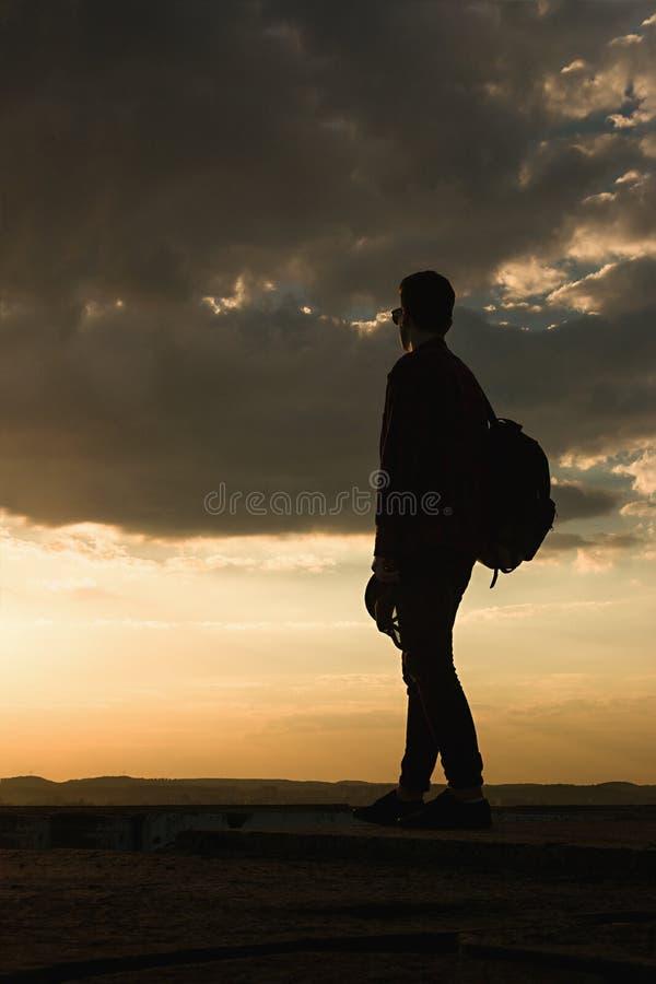 Ein junger kühler Kerl im Hemdrucksack und -Sonnenbrille auf dem Dach während des Sonnenunterganghimmels stockbild
