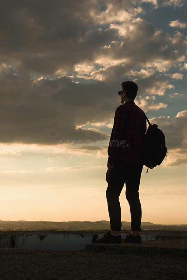 Ein junger kühler Kerl im Hemdrucksack und -Sonnenbrille auf dem Dach während des Sonnenunterganghimmels lizenzfreies stockbild