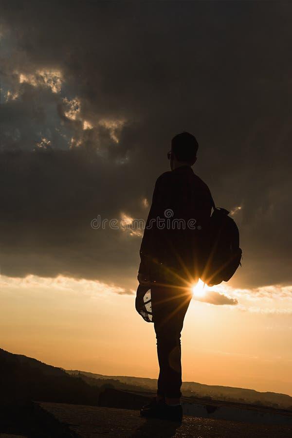 Ein junger kühler Kerl im Hemdrucksack und -Sonnenbrille auf dem Dach während des Sonnenunterganghimmels stockfotografie