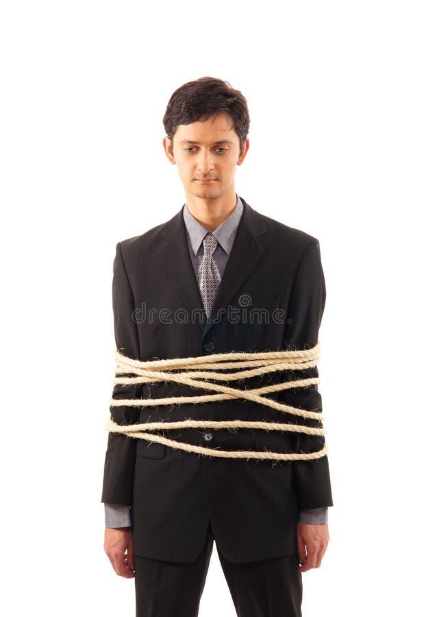 Ein junger kaukasischer Geschäftsmann gebunden in den Seilen stockbild