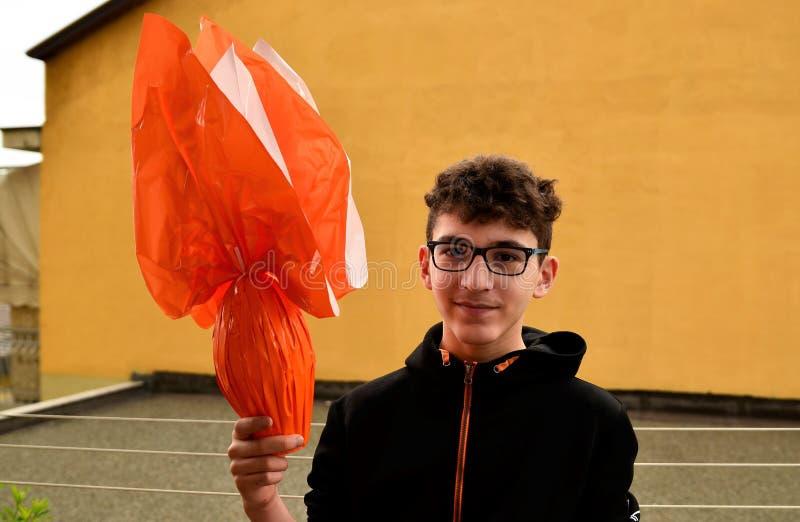 Ein junger kaukasischer Junge, der ein Osterei hält stockbild