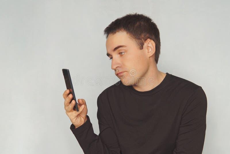 ein junger Kerl betrachtet den Schirm eines schwarzen Smartphone mit einem abweisenden Gefühl auf seinem Gesicht uninteressante K lizenzfreies stockfoto