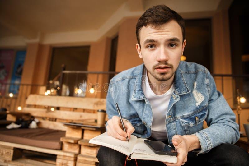 Ein junger Kerl betrachtet die Kamera, hält er ein ntebook und einen Stift Er sitzt auf einer Caféterrasse stockfoto