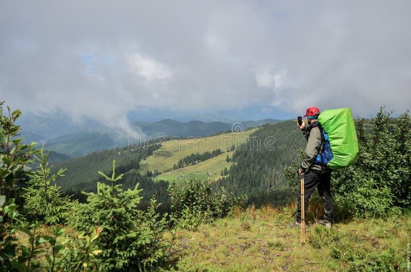 Ein junger Kerl in den Bergen macht ein Foto von  lizenzfreies stockbild