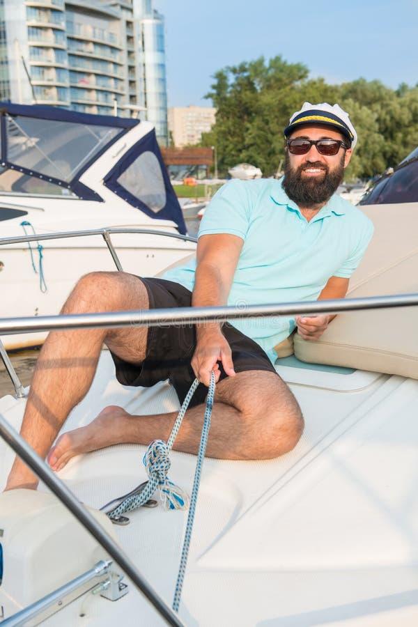 Ein junger Kerl in den Gläsern sitzt auf einer Yacht, die eine Handkurbel zieht stockfotos