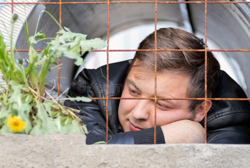Ein junger Kerl, der im Gefängnis betrachtet sitzt, wachsend hinter einer rostigen Gitterlöwenzahnblume Die Gefangenträume der Fr lizenzfreies stockbild