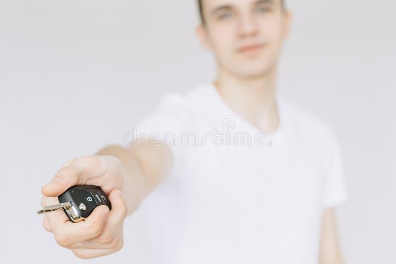 Ein junger Kerl hält die Autoschlüssel in seiner Hand Lokalisierter wei?er Hintergrund lizenzfreie stockfotografie