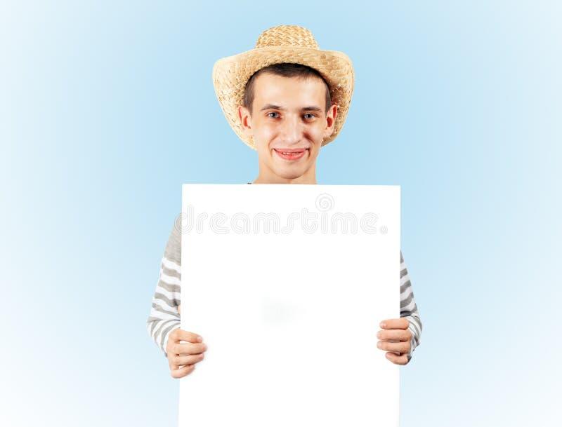 Ein junger Kerl hält eine leere Anschlagtafel stockfotografie