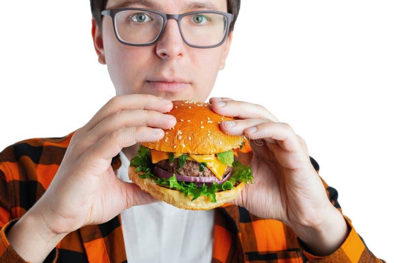 Ein junger Kerl mit den Gläsern, die einen frischen Burger halten Ein sehr hungriger Student isst Schnellimbiß Heiße hilfreiche N stockfoto