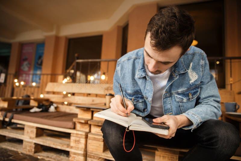 Ein junger Kerl nimmt Kenntnisse beim Sitzen auf der Caféterrasse stockfotografie