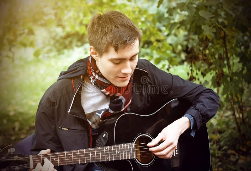 Ein junger Kerl spielt eine schwarze Akustikgitarre und sitzt im Park lizenzfreies stockbild
