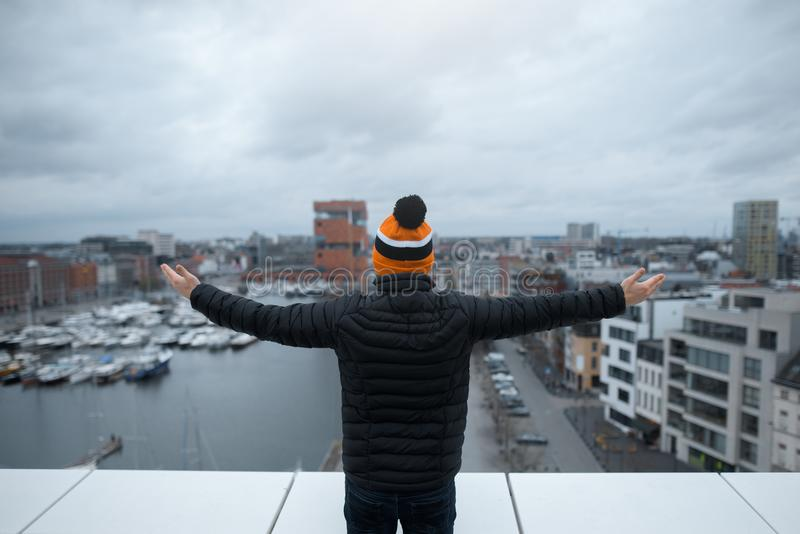 Ein junger Kerlblick auf Stadt vom Dach des Gebäudes mit seinen Armen angehoben Schwarze Jacke und orange Kappe Belgien, Antwerpe stockfotografie