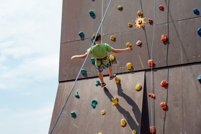 Ein junger Kletterer steigt von einem künstlichen Berg mit Sicherheitsschnüren ab und fängt einen SportVergnügungspark ein stockfoto