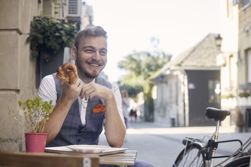 Ein junger lächelnder Mann, 20-29 Jahre alt, tragender Hippie-Anzug, stationierend auf der Straße und draußen essen Brezel vor Bä lizenzfreies stockfoto