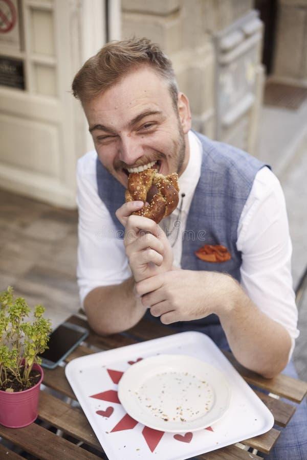 Ein junger lächelnder Mann, 20-29 Jahre alt, tragender Hippie-Anzug, stationierend auf der Straße und draußen essen Brezel vor Bä lizenzfreies stockbild