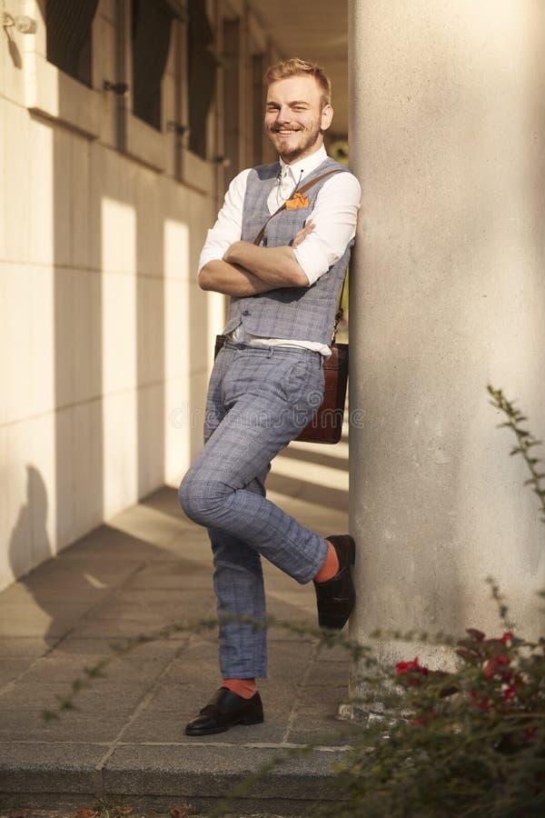 Ein junger lächelnder Mann, 20-29 Jahre alt, tragender Hippie-Anzug, stehend und lehnen sich zur errichtenden Spalte und schauen  stockbilder