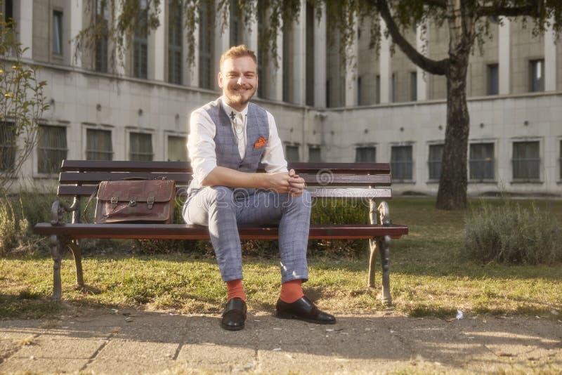Ein junger lächelnder Mann, 20-29 Jahre alt, tragender Retro- Anzug des Hippies, sitzend auf Bank im Stadtparkquadrat lizenzfreies stockfoto